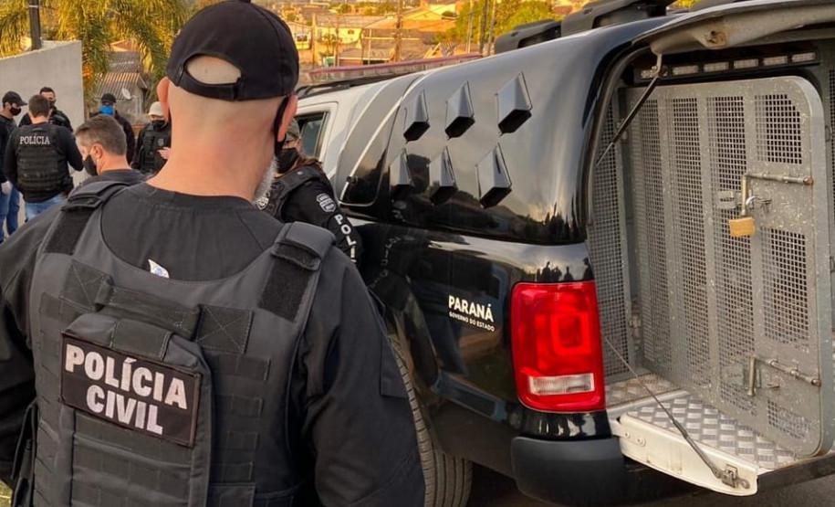 Diversos policiais civis ao lado de viatura