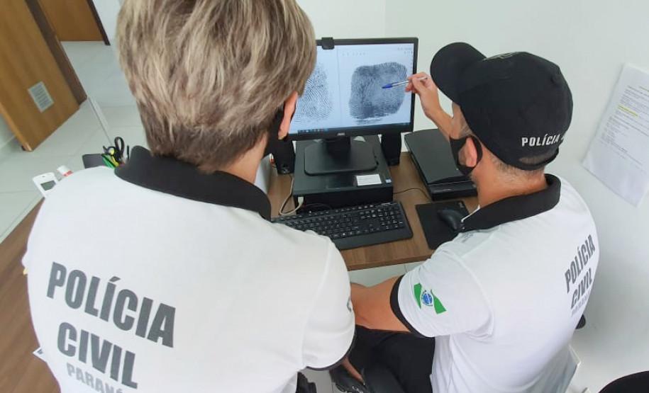 Policiais civis analisam digitais em tela de monitor